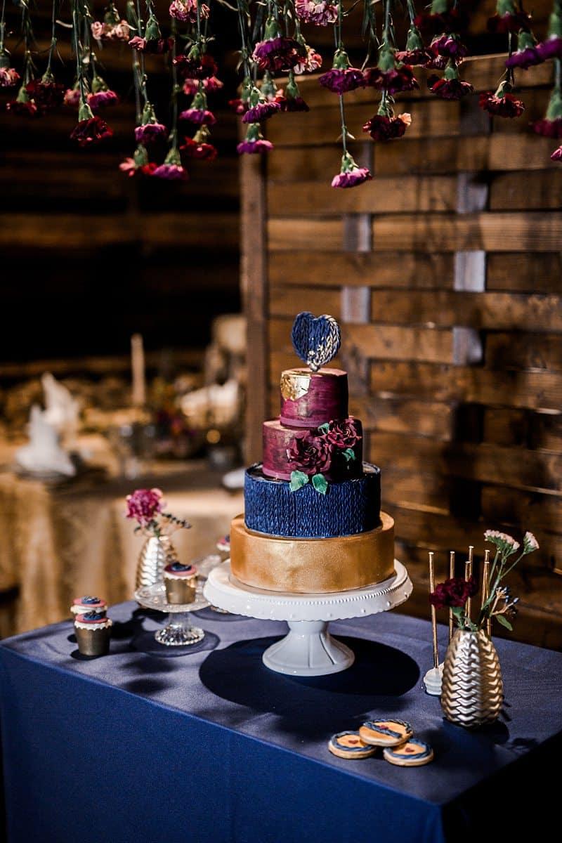 Eine Hochzeitstorte die mit Blumen beschmückt ist.
