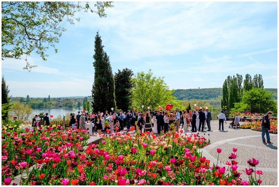 Hochzeitsgäste mit vielen Blumen im Vordergrund.