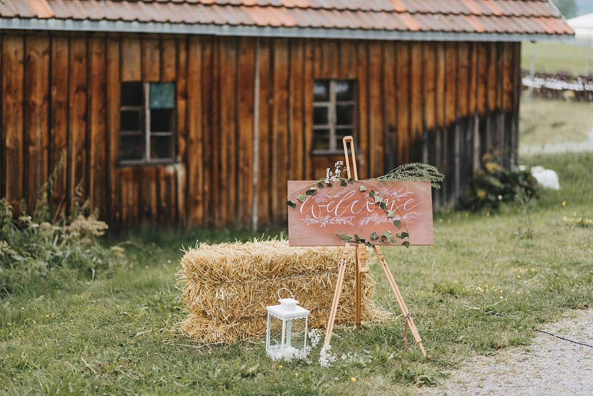 Beschriftete Willkommenstafel und im Hintergrund eine Hol hütte.
