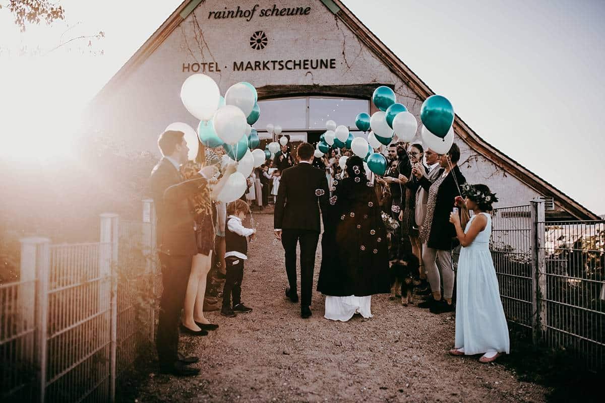 Das Hochzeitspaar mit Hochzeitsgästen und vielen Luftballons.
