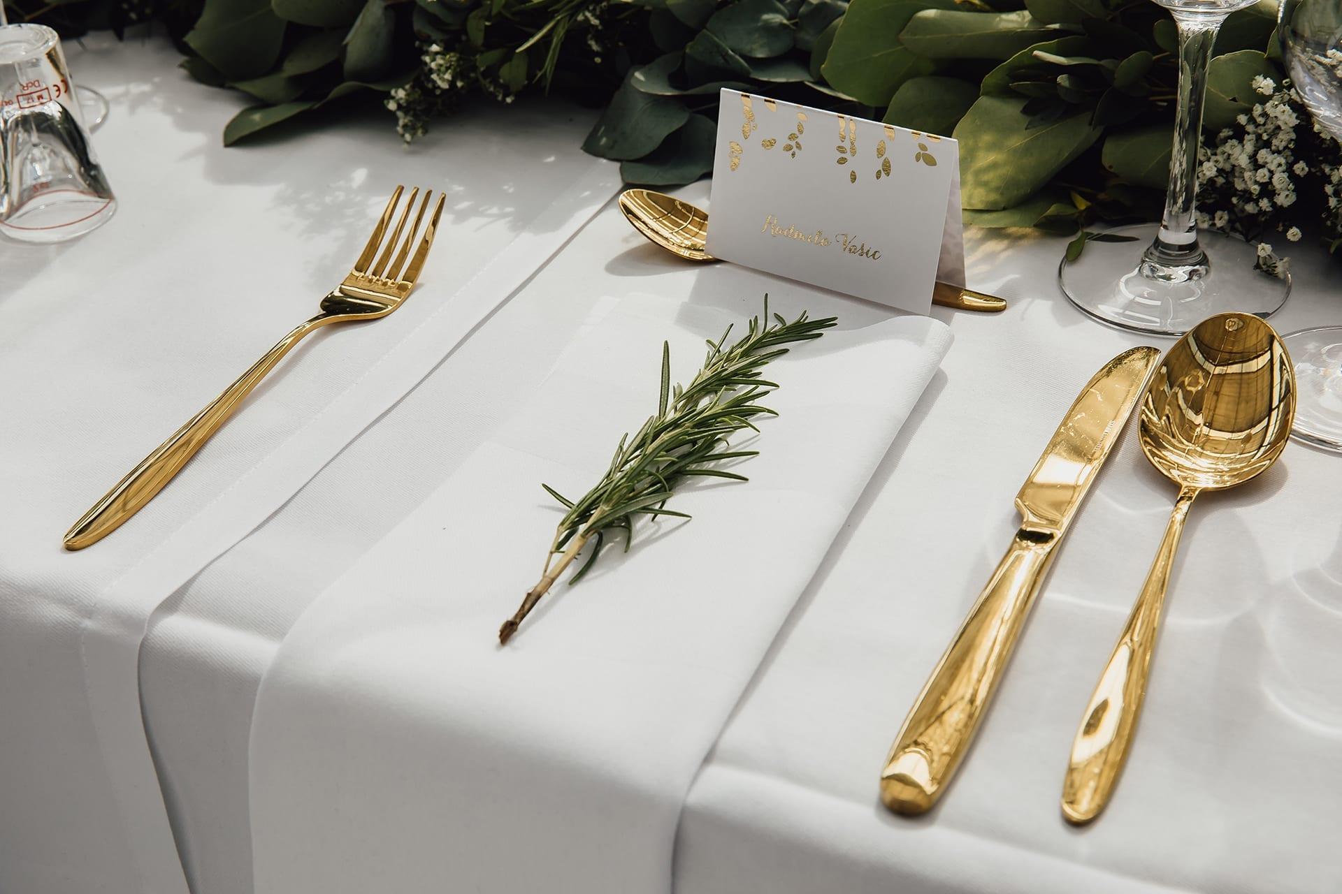 Ein Nadelzweig auf einer Leinenserviette, umgeben von Goldbesteck.
