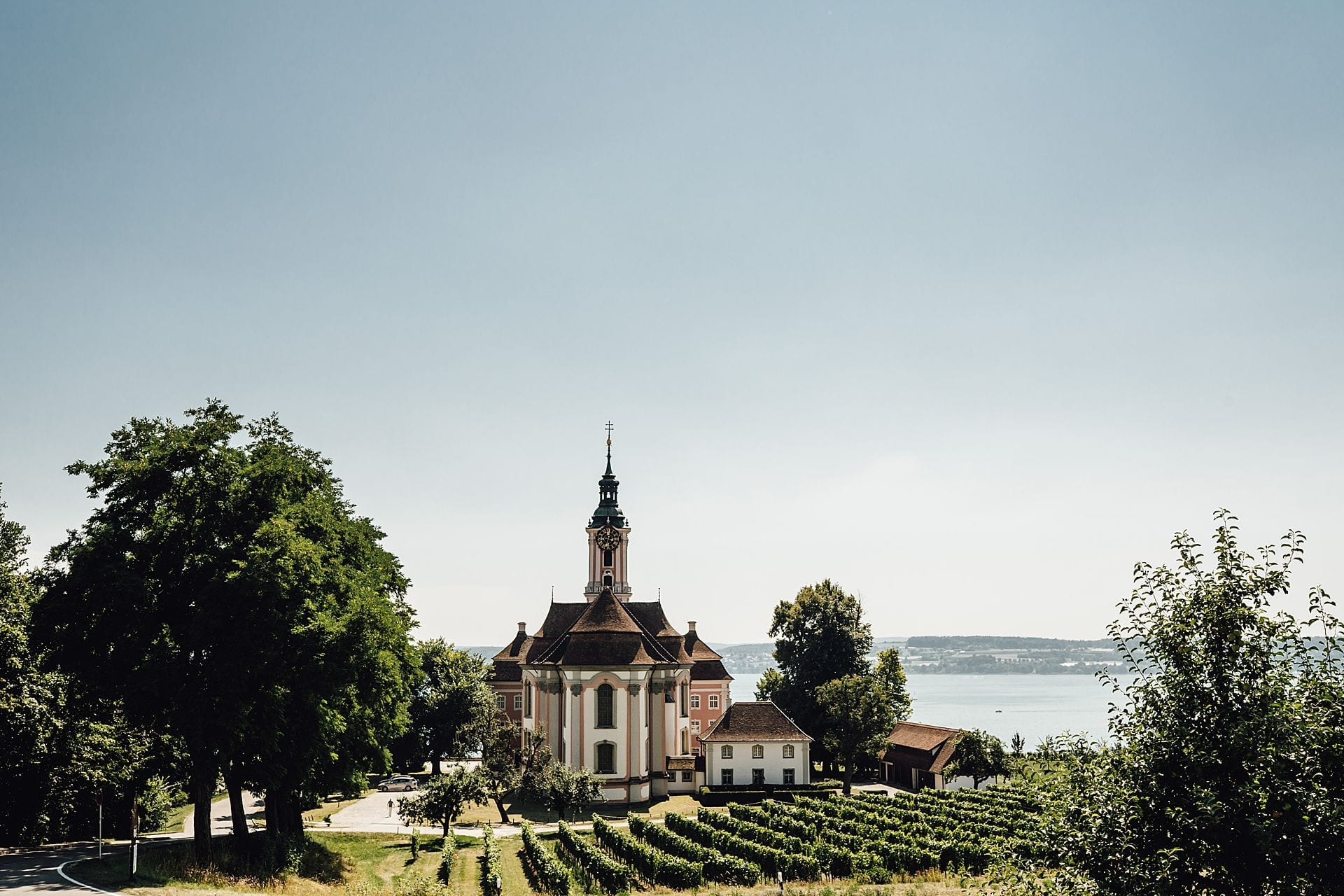 Ein idyllisches Bild einer Kirche vor dem Panorama des Bodensees.