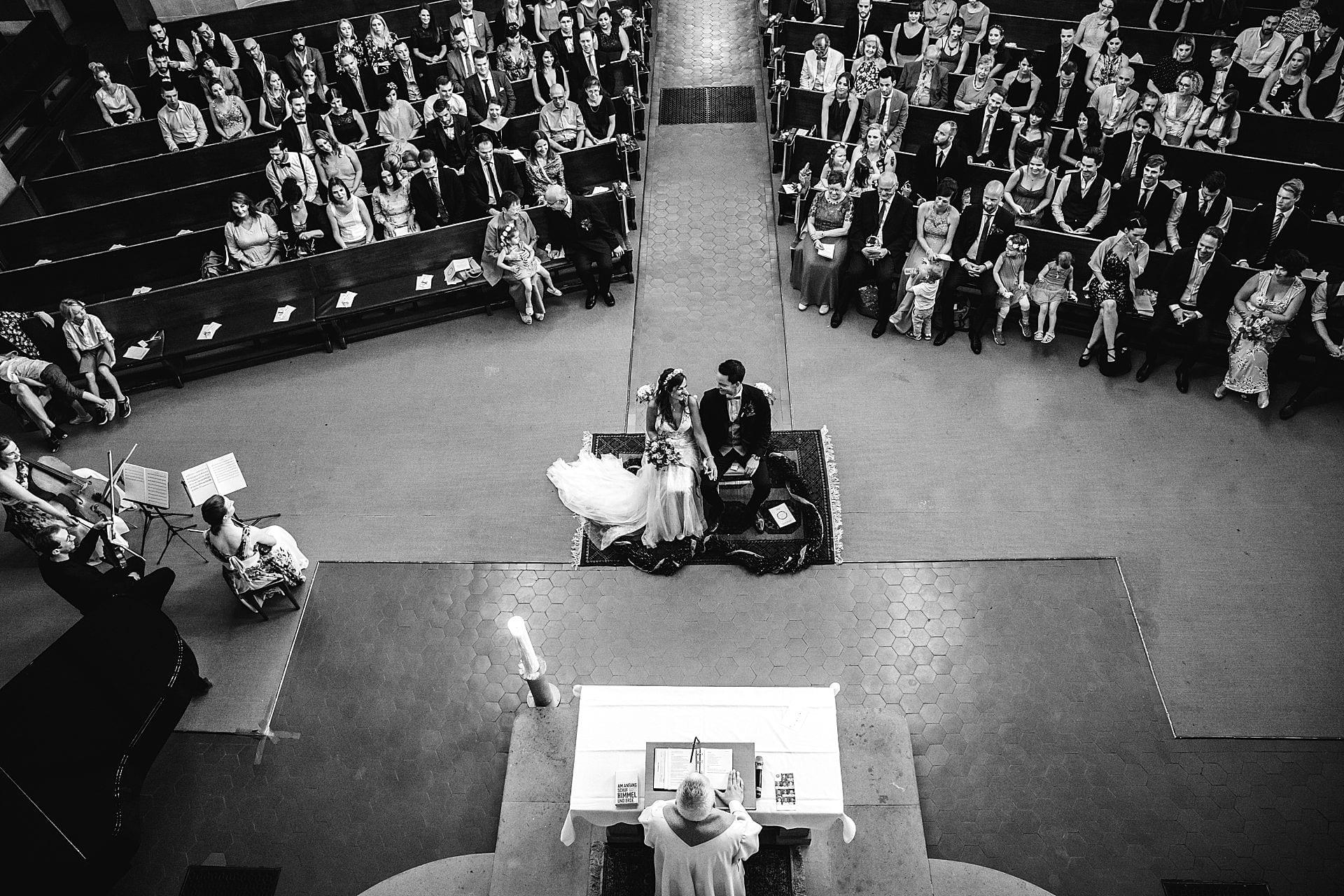 Blick von oben auf das Hochzeitspaar während der kirchlichen Trauung.