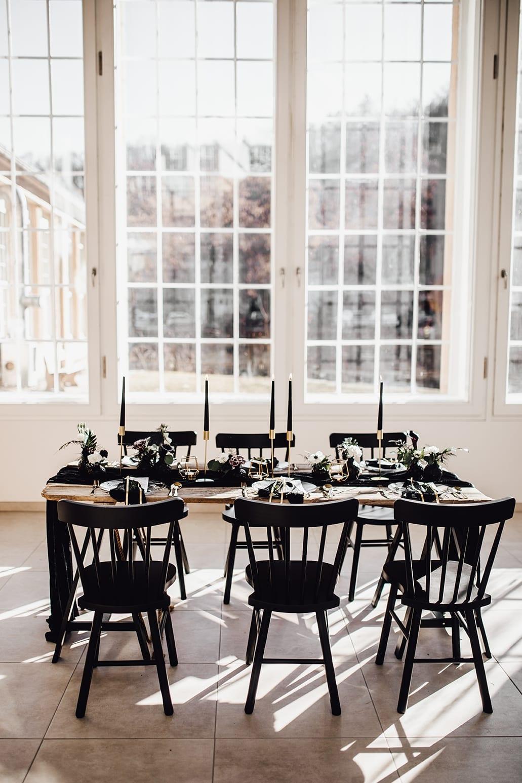 Styled Shoot mit schwarzen Kerzen und Stühlen vor einer Fensterfront.