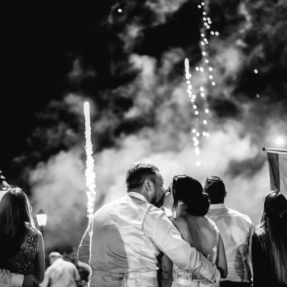 Das Brautpaar küsst sich vor dem Feuerwerk im Hintergrund.