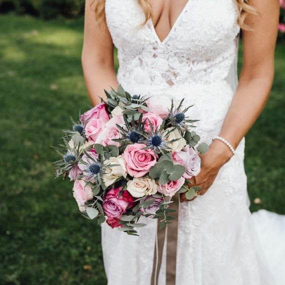 Die Braut hält ihren Brautstrauß.