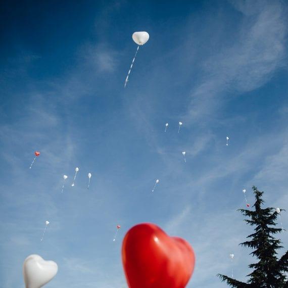 Herzförmige Luftballons steigen in die Luft empor.