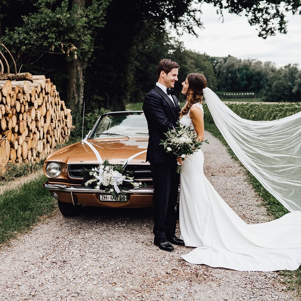 Das sich anlächelnde Brautpaar vor einem alten, amerikanischen Muscle-Car.