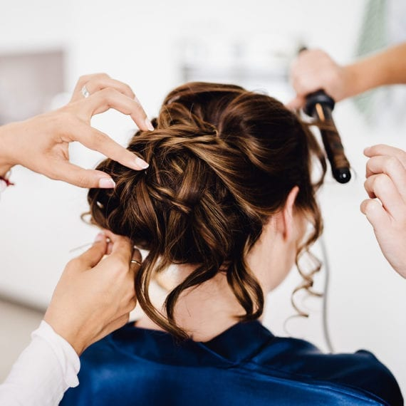 Die Braut, deren Frisur gerade für die Trauung vorbereitet wird.