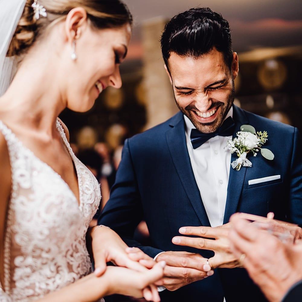 Ein lachender Bräutigam während des Ansteckens der Ringe.