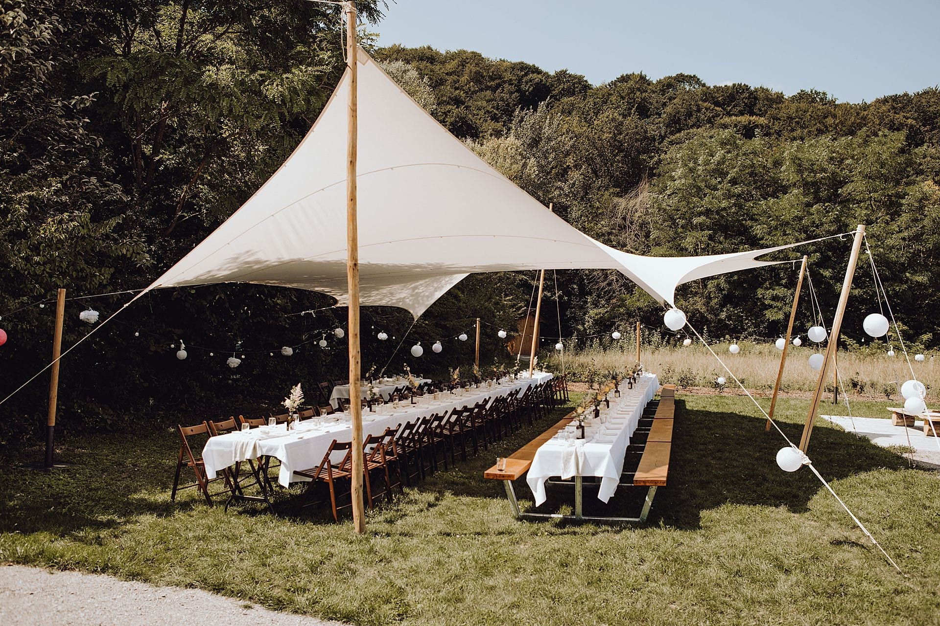 Gedeckte Tische unter einem Stretch-Zelt bei einer outdoor Feier.