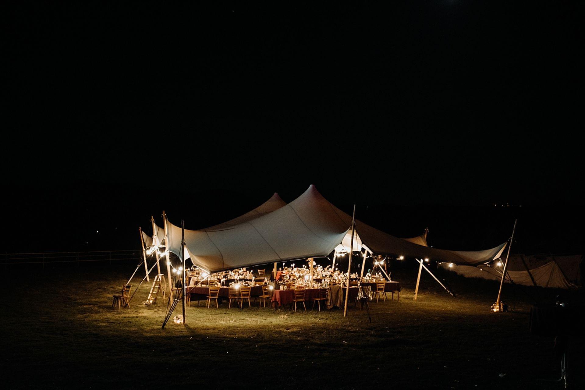 Tische unter einem Zelt mit Lichtern umrandet