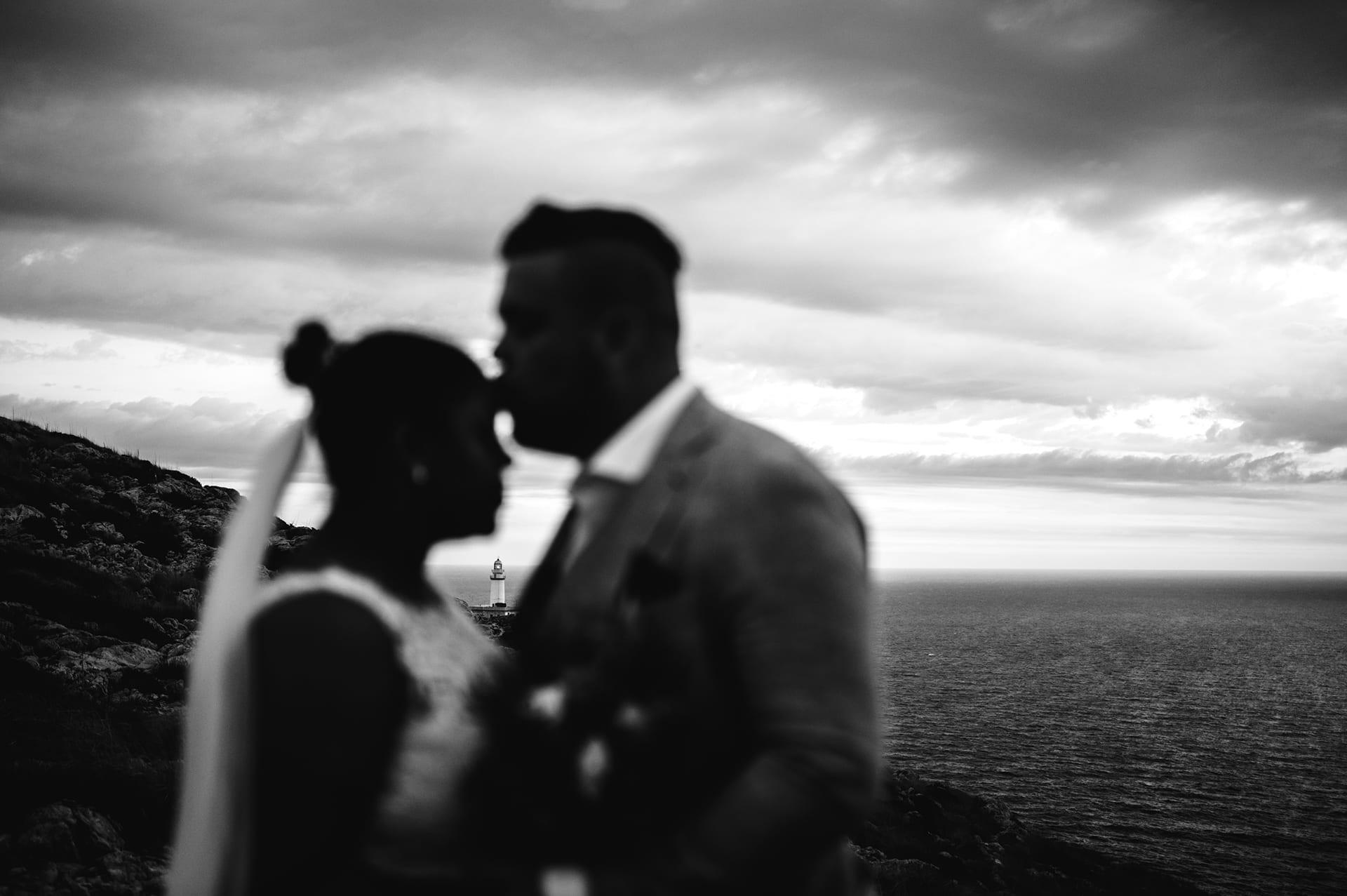 Bräutigam küsst die Braut auf die Stirn, im Hintergrund ein Leuchtturm.