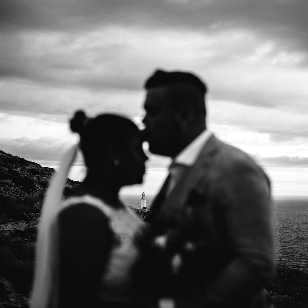 Der Bräutigam küsst die Braut auf die Stirn, im Hintergrund ein Leuchtturm.