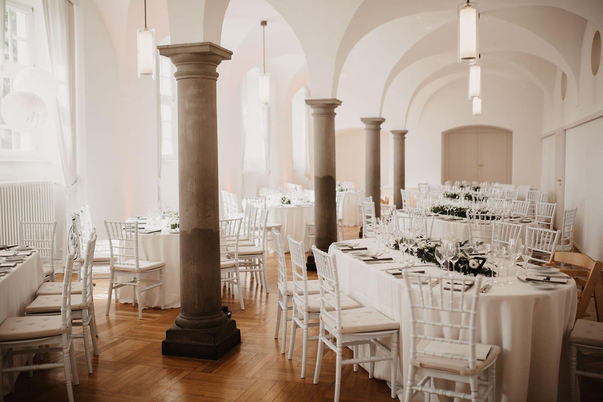 Gedeckte Tische im Speisesaal, umringt von unseren weißen Chiavari Stühlen.