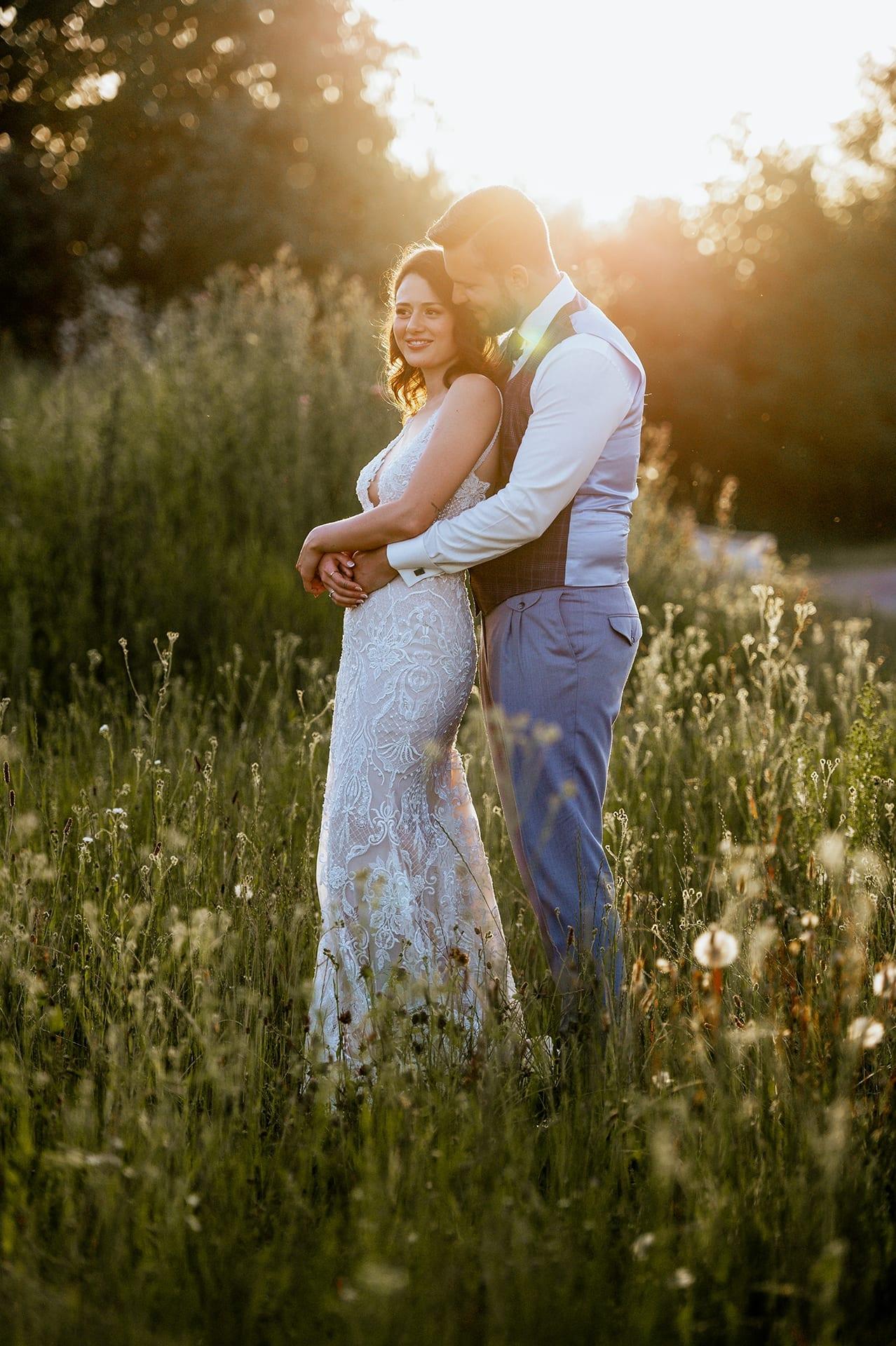 Brautpaar auf einer Wieße mit der Sonne im Hintergrund.