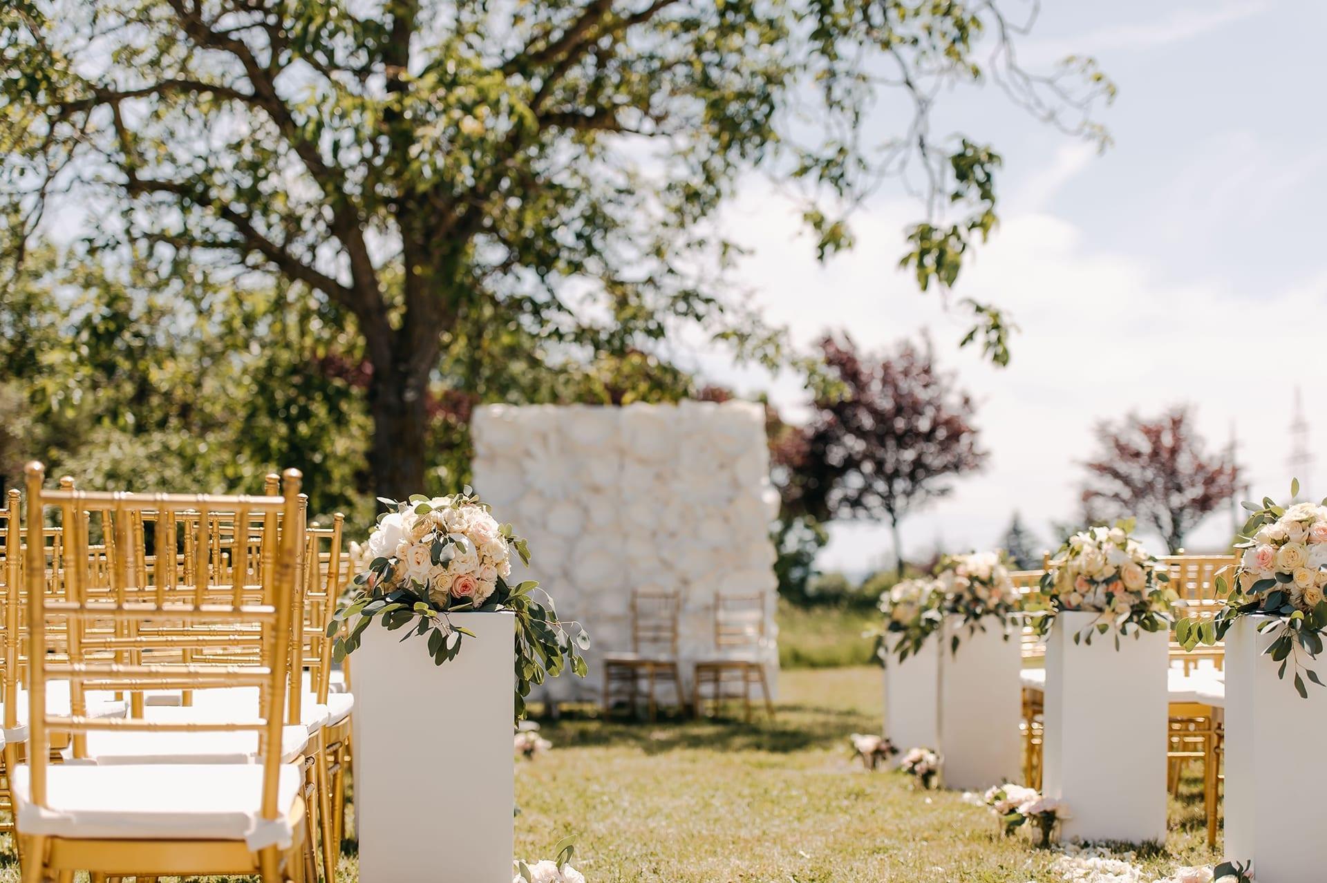 Eine Outdoor Hochzeit mit goldenen Stühlen.